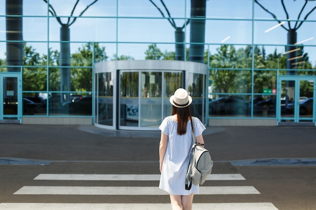 Вид сзади молодой туристической женщины путешественника в шляпе с рюкзаком, стоящей на пешеходном переходе в международном аэропорту
