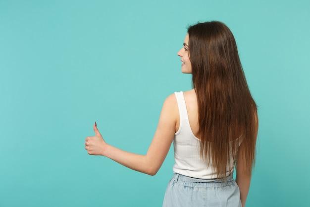 스튜디오에서 파란색 청록색 배경에 고립 된 엄지 손가락을 보여주는 가벼운 캐주얼 옷을 입은 젊은 여성의 후면보기. 사람들은 진심 어린 감정, 라이프 스타일 개념입니다. 복사 공간을 비웃습니다.