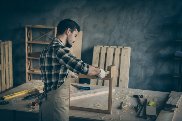 Back rear view  serious confident man using hammer to finish making wooden frame ordered