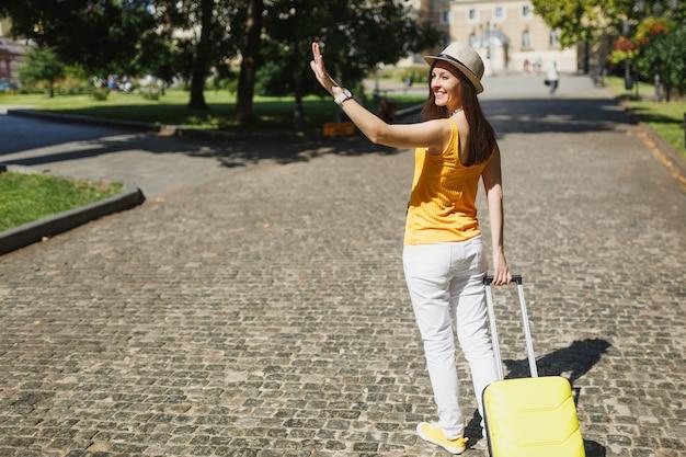 여행가방을 들고 손을 흔들며 인사를 하고 친구들을 만나고 도시 야외에서 산책하는 뒷모습 여행자 관광 여성. 주말 휴가에 해외 여행을 하는 소녀. 관광 여행 라이프 스타일.