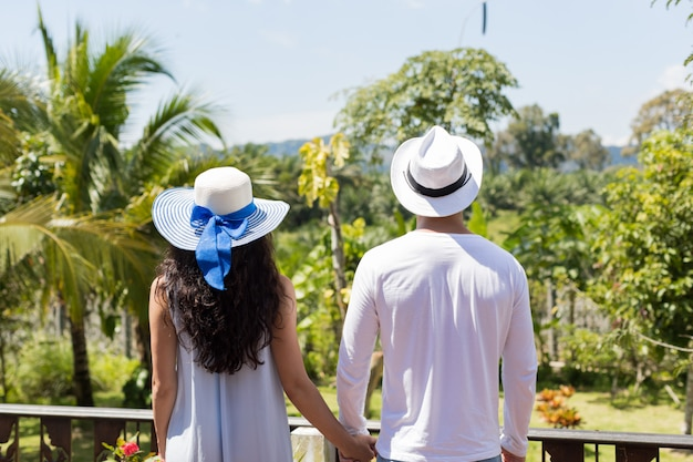 Back rear view of young couple wearing hats holding hands looking at beautiful tropical landscape