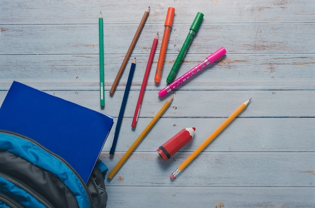Back to scholl crayons and backpack in blue background