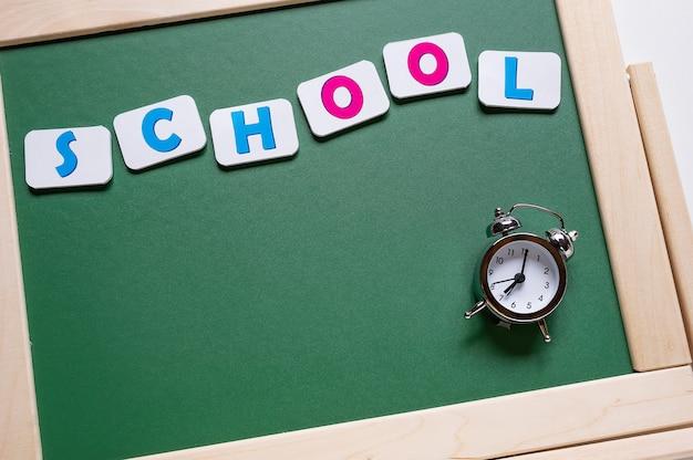 Back to school. alarm clock on the background of the school board. inscription school.