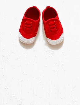 Back to school background - children's cute red small sized canvas shoes top view