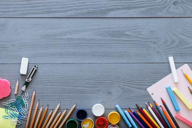 Back to school background concept with free copy space for text, modern supplies stationery, color pencils, paints, paper on dark grey wooden table, modern elementary education, top view