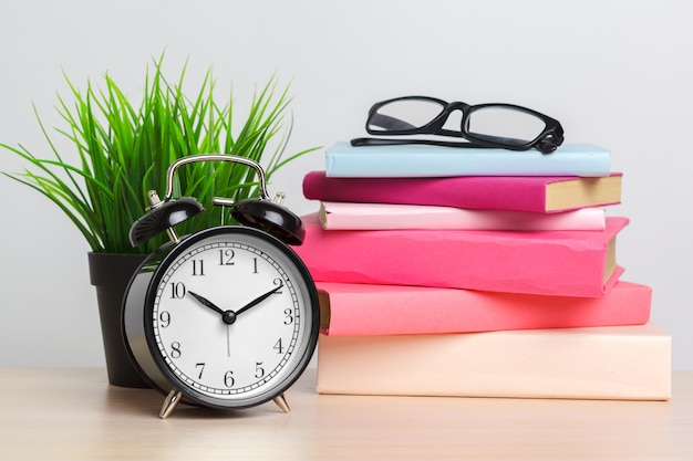 Back to school background with books and alarm clock