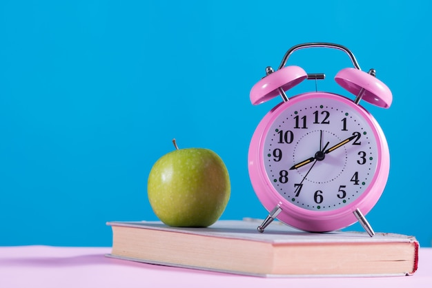 Back to school background with books,apple and alarm clock