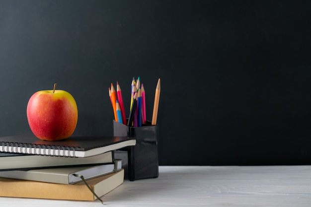 Back to school background with books and apple on blackboard with copyspace