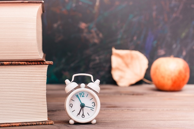 Back to school background with books, clock, apple and fallen leaf over blackboard