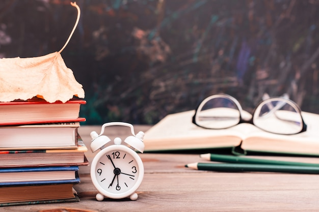 Back to school background with books, clock, fallen leaf, open book and glasses on a wooden table