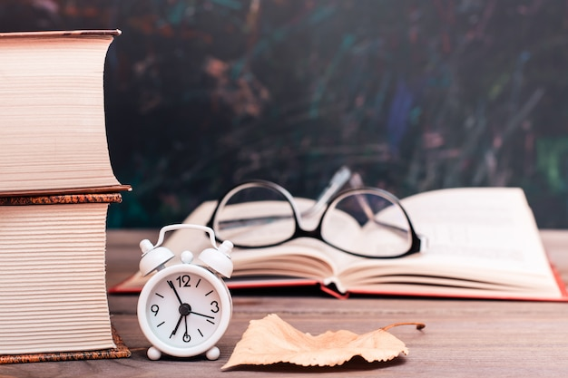 Back to school background with books and clock