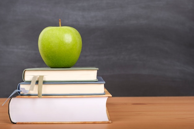 Back to school background with books, pencils and an apple on the school desk.