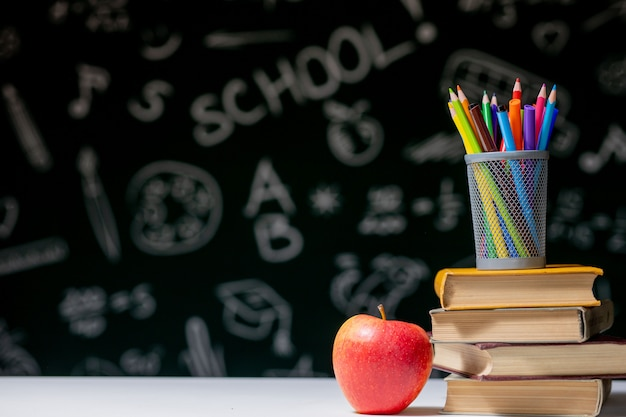 Back to school background with books, pencils and apple on white table.