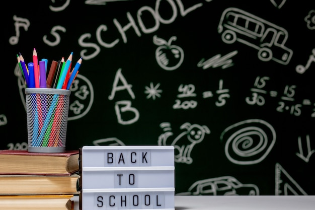 Back to school background with books, pencils and globe on white table on a green blackboard background.