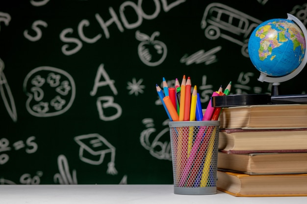 Back to school background with books, pencils and globe on white table on a green blackboard background