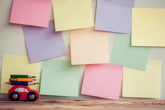Back to school background with miniature red car carrying a colorful pencils over colorful stikers on wall.