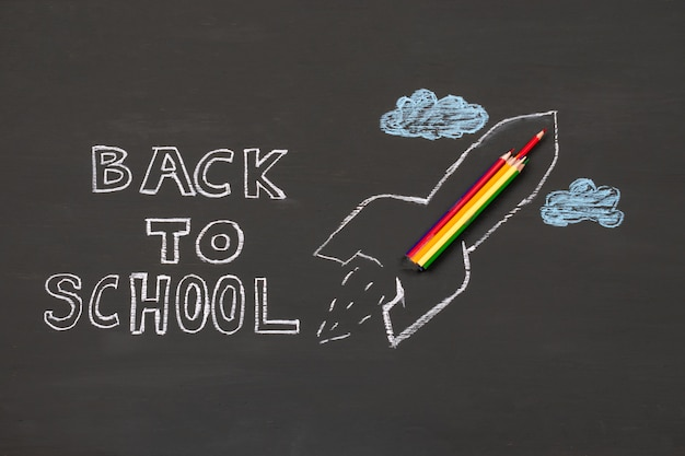 Back to school background with rocket sketch and pencils over chalkboard.