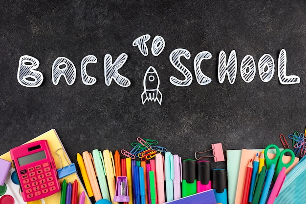 Back to school background with school supplies on chalkboard