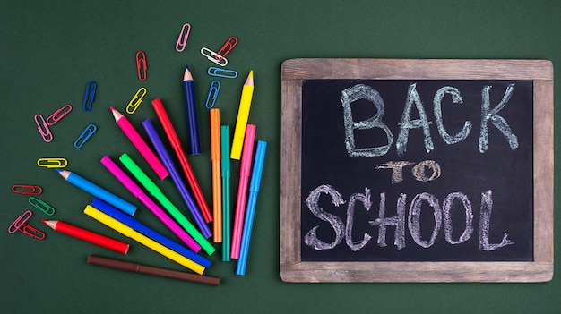 Back to school background with school supplies and chalkboard