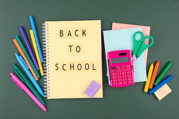 Torna a scuola sfondo con materiale scolastico e taccuino