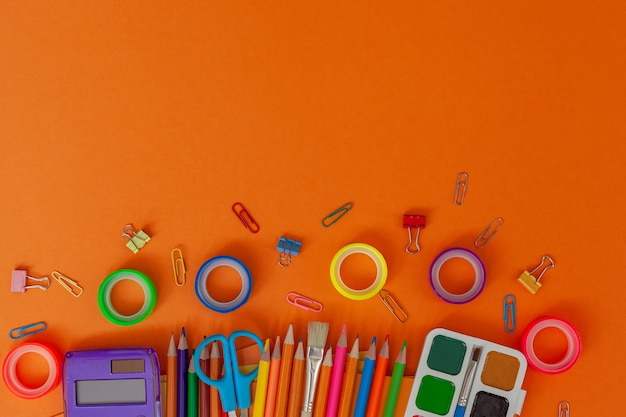 Back to school background with school supplies on orange table. top view from above