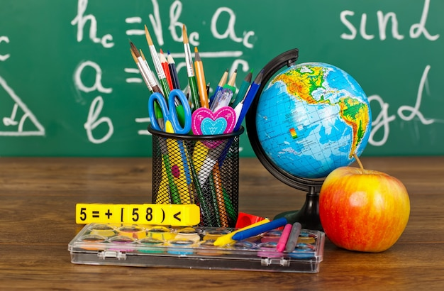 Back to school - blackboard with pencil-box and school equipment on table