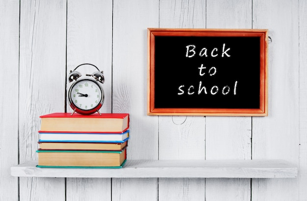 Back to school. books and an alarm clock on wooden shelf