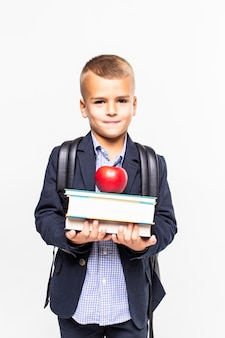 Back to school. books, apple, school, kid. little student holds books. cheerful smiling little child against blackboard. school concept
