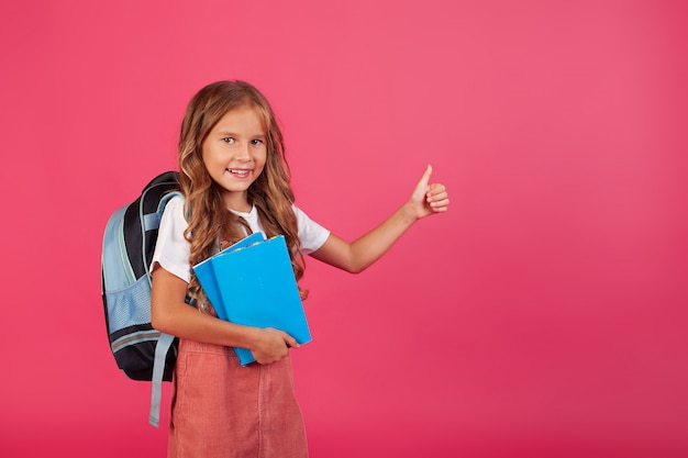 Back to school. cheerful happy girl with a blue backpack on a pink background.