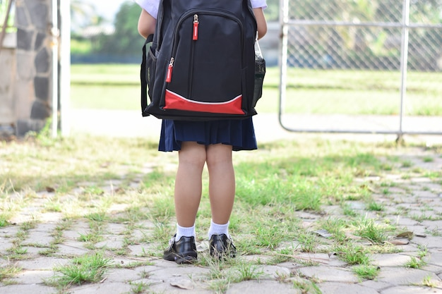 Back to school, child girl with bag go to elementary school.