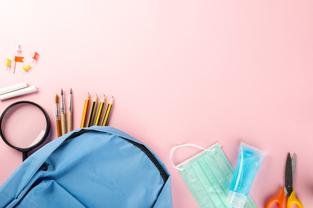 Back to school or college concept school supplies stationery backpack and surgical face mask
