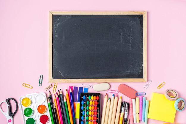 Back to school color chalk pencil  stationery on pink blackboard background.