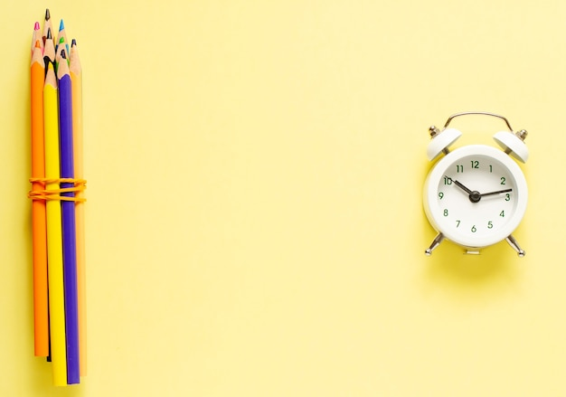Back to school. colored pencils and an alarm clock on a yellow paper background. copy space