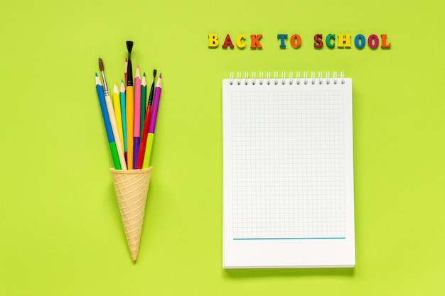 Back to school and colored pencils paintbrush in waffle ice cream cone and notebook on green background.