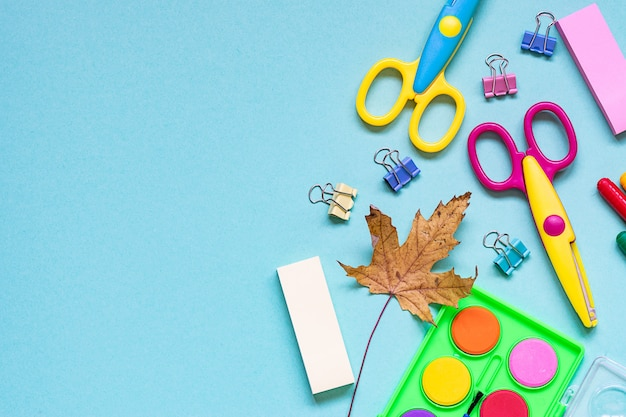 Back to school composition with bright stationery set on blue background.
