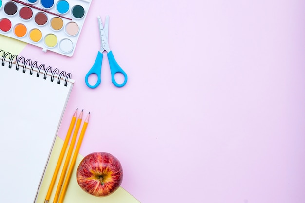 Back to school composition with copy space on the right on pink and yellow background