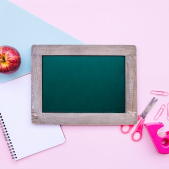 Back to school composition with green slate for mock up on light blue and pink background