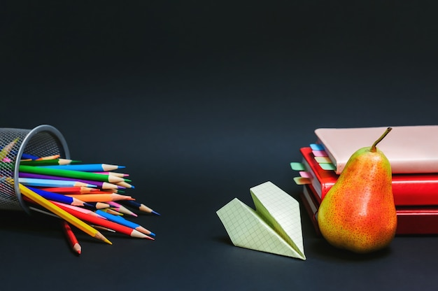 Back to school composition with paper plane and pear