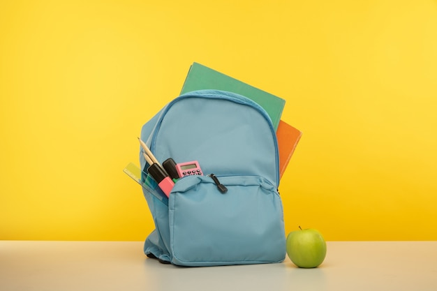 Back to school concept backpack with school supplies on yellow background