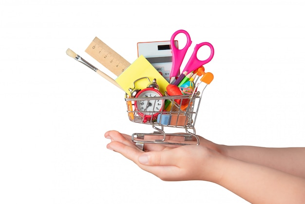 Back to school concept. bright stationery items in a mini supermarket trolley in hand isolated on white