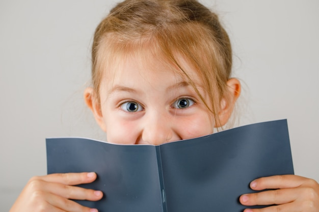 Back to school concept close-up. little girl holding opened copybook.