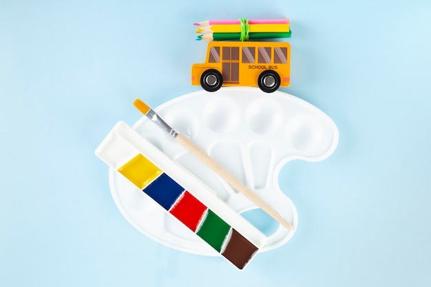 Back to school concept. drawing accessories. toy school bus drives palette, on blue background. top view