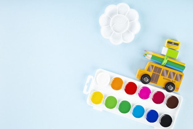 Back to school concept. drawing accessories. toy school bus drives watercolor, on blue background. top view. copy space