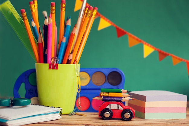 Back to school concept. group of school supplies: paint, pencils, paper, notepad on wooden table
