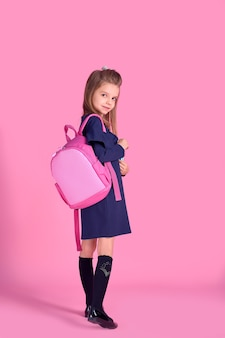 Back to school concept half turned photo portrait of lovely confident beautiful clever girl with copybook notebook wearing school uniform dress pink bright backpack isolated