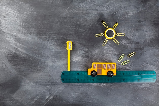 Back to school concept. imitation of trip to school on school bus. pencils, ruler, sharpener, toy bus on black background. top view. copy space