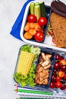 Back to school concept. lunch box with healthy fresh food. sandwich, vegetables, fruits and nuts in food container, light background.