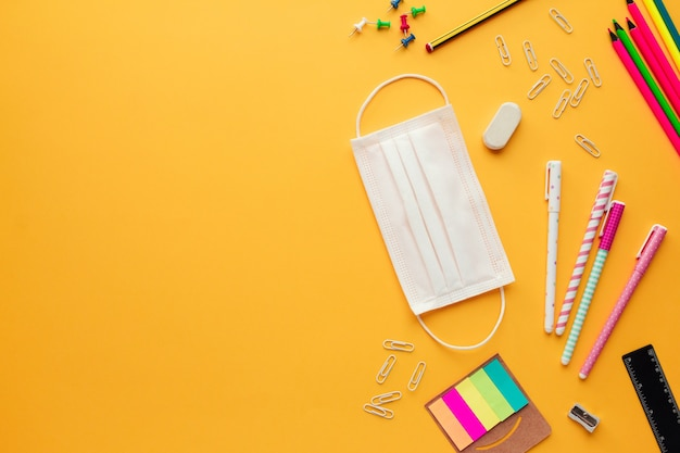 Back to school concept in the new normal with a face mask, some stationery objects