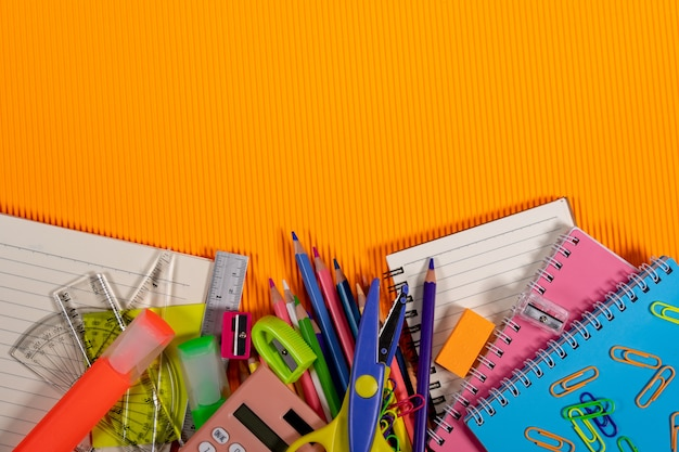Back to school concept. notebook and education equipment on orange background.