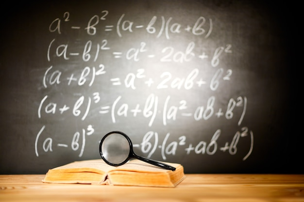 Back to school concept. old schoolbooks and magnifier lying on a wooden school desk in front of a black chalkboard with mathematical formulas school.